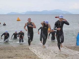 琵琶湖の浜を駆け上がるトライアスロン参加者