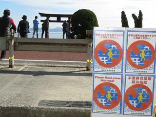 白髭神社前の国道に設置された3カ国語で横断の危険を訴える看板とそれを無視して横断する観光客