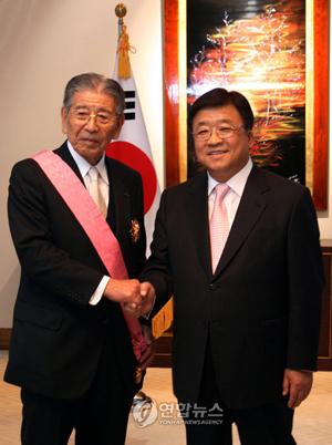 日本の単独開催を阻止して日韓共同開催を実現させた功労者である電通の成田豊は、韓国政府から外国人に与えられる勲章としては最高位の勲章(修交勲章光化章)を授与された。
