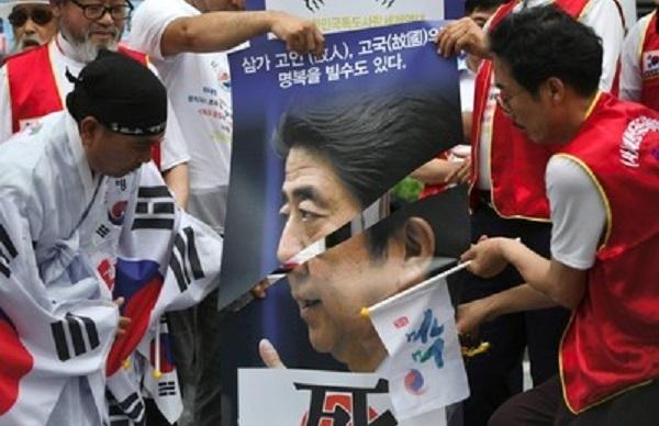 韓国・ソウルの在韓日本大使館近くで、デモ参加者に切られた安倍晋三首相の顔が描かれた印刷物(2019年7月23日撮影)