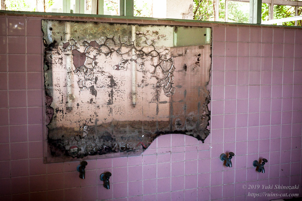 女子大浴場に掛けられた溶け落ちるように劣化した鏡
