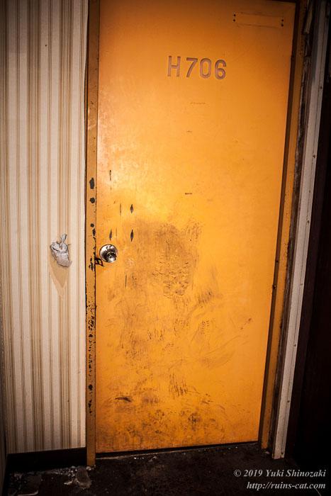 壊してこじ開けようとして途中で諦められたH706号室のドア。蹴り跡やノブの横の壁を抜こうとした跡が残っている。