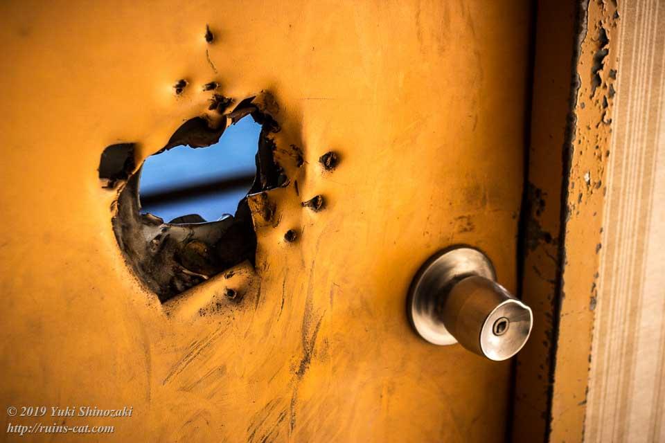 バールのようなものでぶち抜かれた金属製の客室ドア
