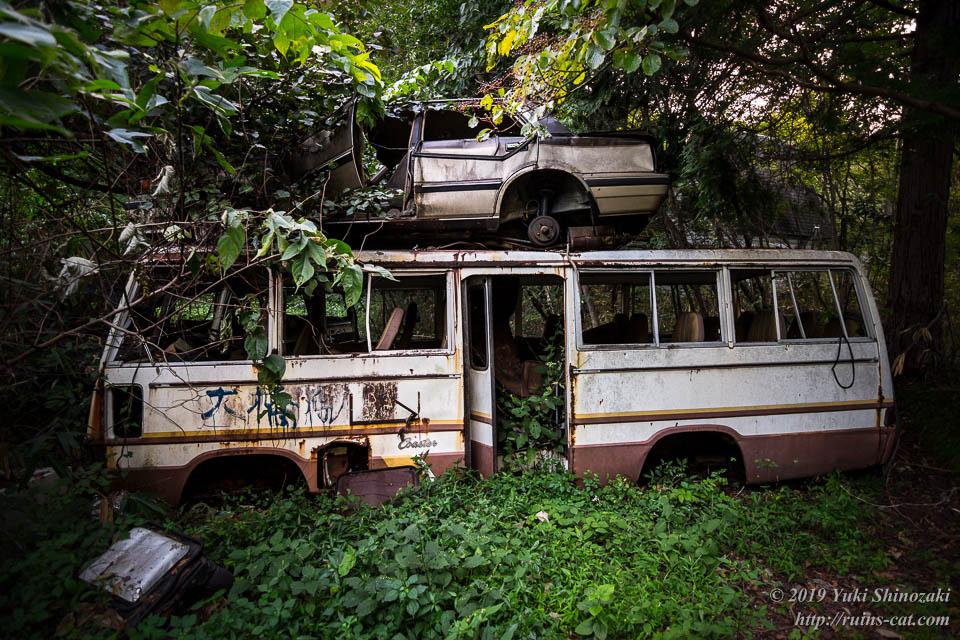 ファミテックの送迎バスの廃車の上にさらに廃車。緑に飲み込まれようとしている。